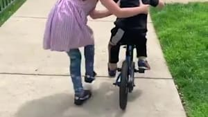 Adorable girl coaches little brother to ride bike