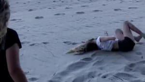 Girl falls off rope swing on beach