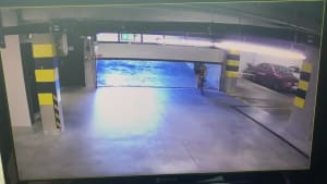 Cyclist slams into garage door of parking lot