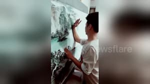 Talented man uses arm, palm to draw landscapes