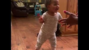Baby takes first steps while mom and sibling cheer