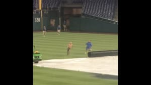 Man slides on water-filled tarp on baseball field