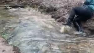 Boy tries to jump across stream and slips