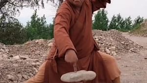 Kung fu monk breaks a cobblestone with two fingers