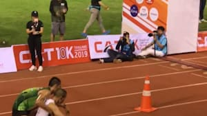 Racer stops to help runner cross the finish line