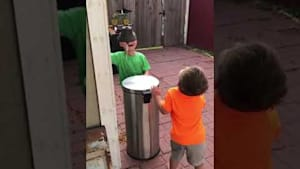 Kids jokingly hit each other with trash can lid