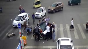 Motorists and passersby lift up car after woman is trapped underneath it on Chinese road