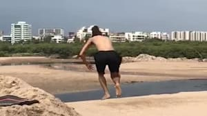 Guy attempts backflip over sand mound and falls