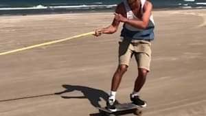 Guy skateboarding on beach falls