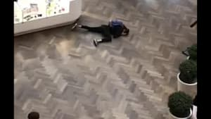Guy pretends to trip over sign and crawls on floor