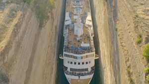 Enormous cruise ship squeezes through tight canal