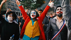 Protesters around the world dress  as the 'Joker'