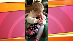 Proud 3-year-old cuddles her newborn baby sister