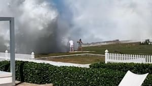 Couple gets knocked over by a massive wave