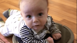 Adorable baby catches a ride with Roomba vacuum