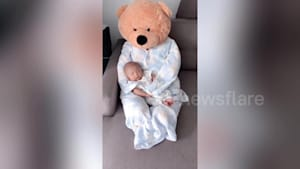 Chinese mother uses giant cuddly toy to soothe crying baby