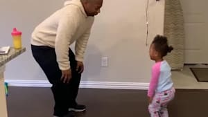 Dad teaches toddler daughter dance steps