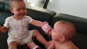 Toddler feeds baby sister from bottle