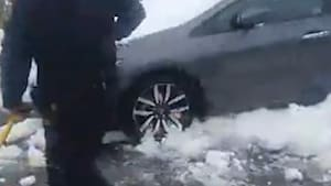 NYPD aid woman whose car is stuck in a snow pile