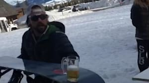 Bros toss each other a beer using a snowboard
