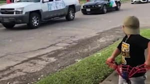 People parade with cars for kid's birthday