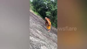 Buddhist monk walks up mountain without ropes