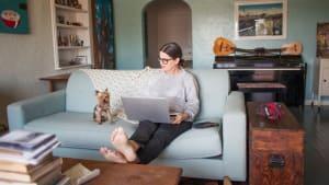 Junge Frau sitzt nach einem entspannten Abend auf dem Sofa plötzlich im Rollstuhl