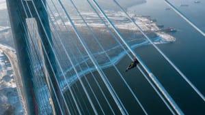 Nichts für Menschen mit Höhenangst: Brückenarbeiter entfernen Eisablagerungen