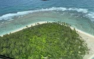 Three rescued from Pacific island after writing SOS in sand