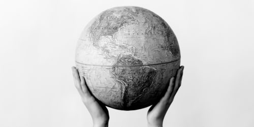 Two hands hold up a globe.