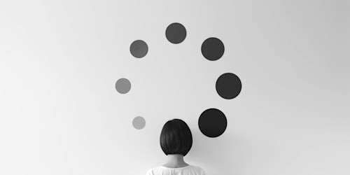 A woman looks at a series of artistic dots on the wall.