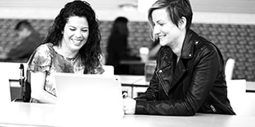 Two smiling women review information on a laptop.