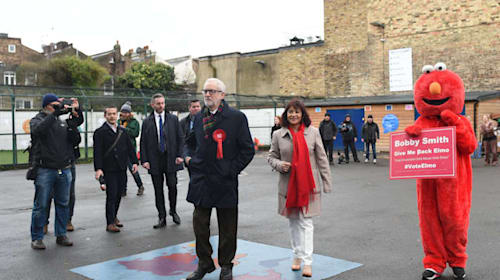 Protester dressed as Elmo greets Jeremy Corbyn at polling station