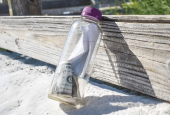 Off-duty officer finds bottle with ashes and a note with $4 bills floating in sea