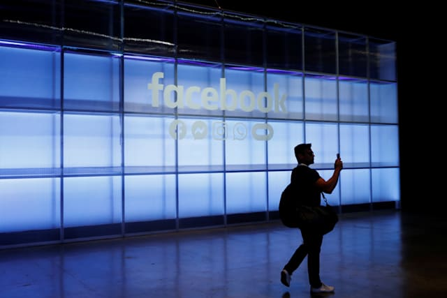 An attendee takes a photograph of a sign during Facebook Inc's F8 developers conference in San Jose, California, U.S., April 30, 2019.  REUTERS/Stephen Lam