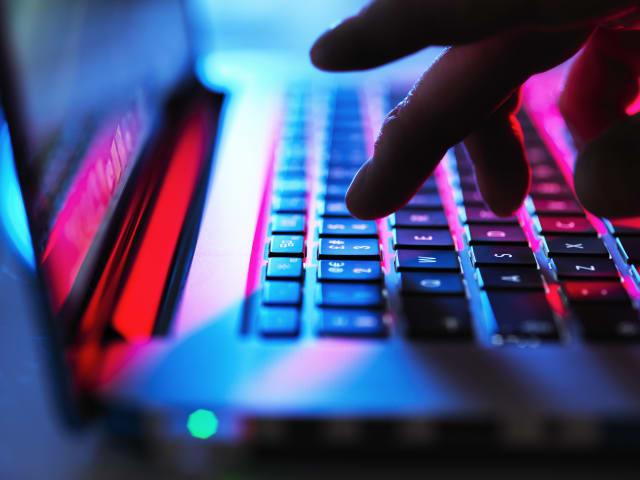 Man typing at his laptop computer at night