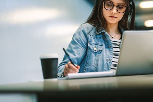 University student writing in a book while sitting at desk with laptop and coffee up at college campus. Female student studying at college library.