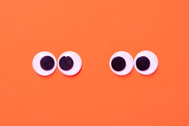 Googly eyes: One pair strabismus and squint mad googly eyes and one pair normal funny eyes next to each other on a orange background.