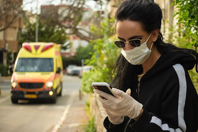 Anti-virus concept. Woman wearing Mask and Glasses Waiting for Ambulance. Copy Space