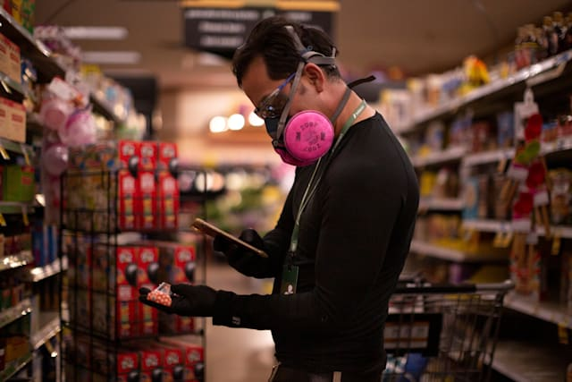 Instacart employee Eric Cohn, 34, uses his phone to scan an item for a delivery order he is preparing from Fry's grocery store while wearing a respirator mask to help protect himself and slow the spread of the coronavirus disease (COVID-19) in Tucson, Arizona, U.S., April 4, 2020. Picture taken April 4, 2020. REUTERS/Cheney Orr