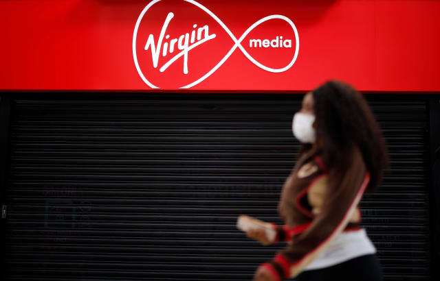 """A person wearing PPE (personal protective equipment), including a face mask as a precautionary measure against COVID-19, walks past a Virgin Media mobile phone store, closed-down due to the novel coronavirus pandemic, in London on May 4, 2020. - Spanish group Telefonica on Monday said it was in talks with US cable giant Liberty Global to merge their telecoms operations in the UK. In a statement, Madrid-based Telefonica said it was in """"talks... about a possible integration"""" of its O2 mobile business and Liberty's Virgin Media that provides a mix of telecoms and television services, while providing caution over a deal ending up being struck. (Photo by Tolga Akmen / AFP) (Photo by TOLGA AKMEN/AFP via Getty Images)"""