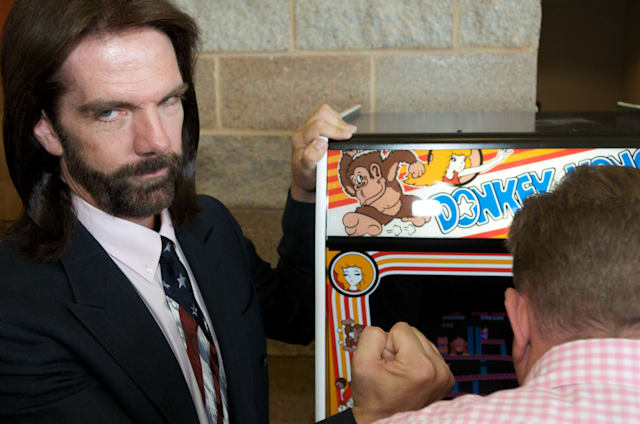 OTTUMWA, IA - AUGUST 13: Billy Mitchell, the Video Game Player of the Century, poses while Steve Sanders, 'The Orignal King of Kong,' plays Donkey Kong at the launch party for the International Video Game Hall of Fame and Museum on August 13, 2009 in Ottumwa, Iowa. Ottumwa was officially proclaimed the Video Game Capital of the World at the launch party and plans are underway to build a full museum in the small Iowa city. The rivelry of Sanders and Mitchell is documented in the movie 'The King of Kong' where they played each other for the best score ever. (Photo by David Greedy/Getty Images)