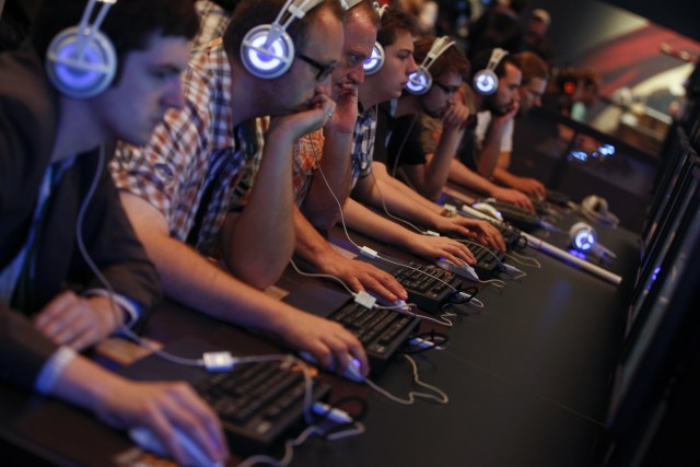 """Visitors play """"Hearthstone"""" at the World of Warcraft exhibition stand during the Gamescom 2013 fair in Cologne August 21, 2013. The Gamescom convention, Europe's largest video games trade fair, runs from August 22 to August 25. REUTERS/Ina Fassbender (GERMANY - Tags: BUSINESS ENTERTAINMENT)"""