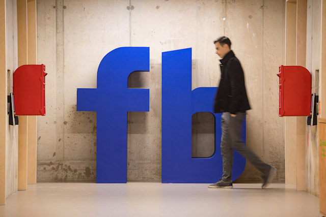 A man walks past a Facebook logo at Facebook's new Frank Gehry-designed headquarters at Rathbone Place in London. (Photo by Dominic Lipinski/PA Images via Getty Images)