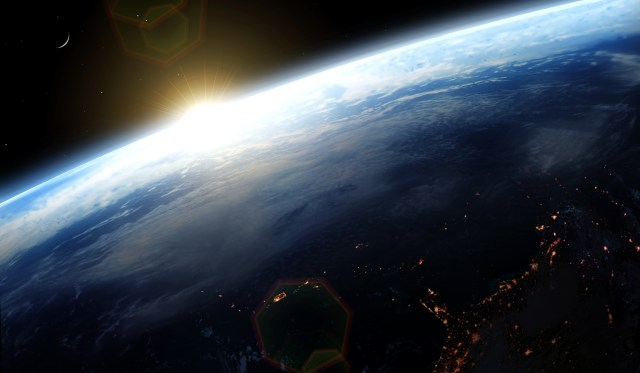 Illustration of the Sun rising over the Earth, as seen from space. The moon is seen off to the left. On the dark side of the Earth, cities can be seen illuminating the night.