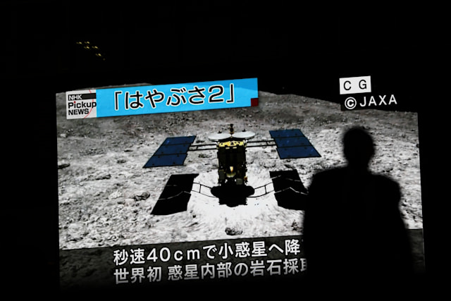 In this picture taken on July 10, 2019 a man walks past a screen displaying a computer-generated image of the Hayabusa2 probe, during a news broadcast at Akihabara district in Tokyo. - Japan's Hayabusa2 probe landed successfully on a distant asteroid for a final touchdown on July 11, 2019, hoping to collect samples that could shed light on the evolution of the solar system. (Photo by Behrouz MEHRI / AFP)        (Photo credit should read BEHROUZ MEHRI/AFP/Getty Images)