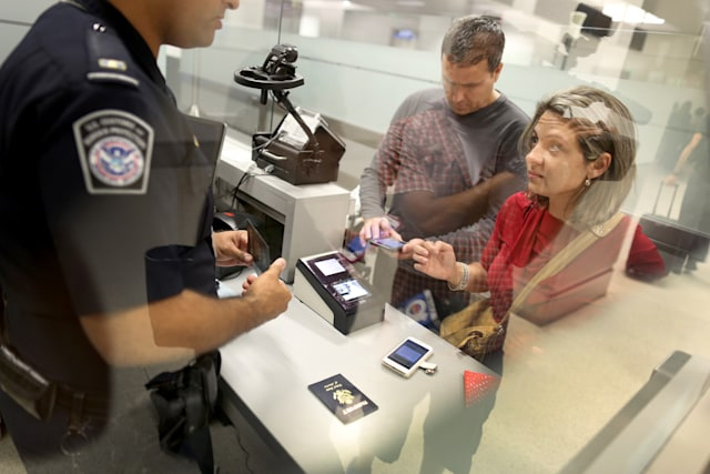 MIAMI, FL - MARCH 04:  Leonel Cordova (L) and Noris Cordova speak to a CBP officer as they try to use their new mobile app at an entry point as the program is  unveiled for international travelers arriving at Miami International Airport on March 4, 2015 in Miami, Florida. Miami-Dade Aviation Department and U.S. Customs and Border Protection (CBP) unveiled a new mobile app for expedited passport and customs screening. The app for iOS and Android devices allows U.S. citizens and some Canadian citizens to enter and submit their passport and customs declaration information using their smartphone or tablet and to help avoid the long waits in the exit lanes.  (Photo by Joe Raedle/Getty Images)
