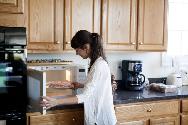 Woman cooking in the kitchen, using microwave