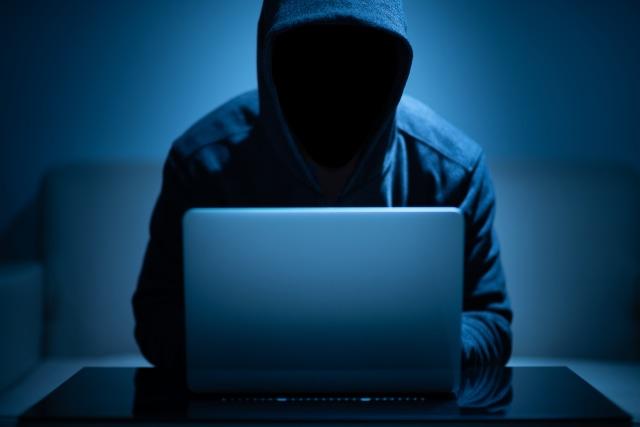 Hacker dark face using laptop in the dark room