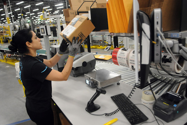 An Amazon associate processes a package for delivery at the newest Amazon Robotics fulfillment center during its first public tour on April 12, 2019 in the Lake Nona community of Orlando, Florida. The over 855,000 square foot facility opened on August 26, 2018 and employs more than 1500 full-time associates who pick, pack, and ship customer orders with the assistance of hundreds of robots which can lift as much as 750 pounds and drive 5 feet per second.  (Photo by Paul Hennessy/NurPhoto via Getty Images)